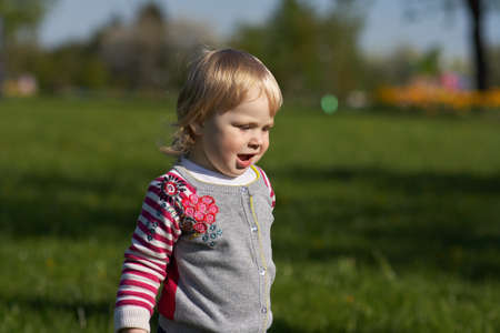 The girl in the park sitting on the green grass