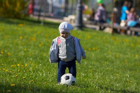 Little active football fan running on the green grass field with ball