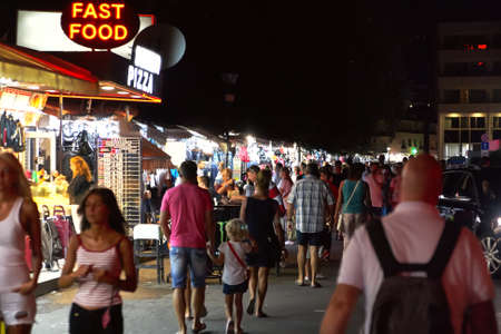 Crowded nightly walk among shops, bars and small sellers on the beach in Bulgaria in the resort White Beach in August