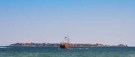 Historic pirate ship in the ocean near the islands and beautiful panorama Stock Photo