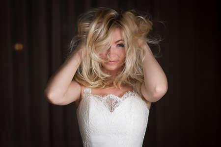 Shaggy belle femme aux cheveux blonds sur fond sombre Banque d'images - 57955064