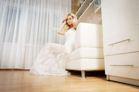 Young beautiful bride is sitting at room