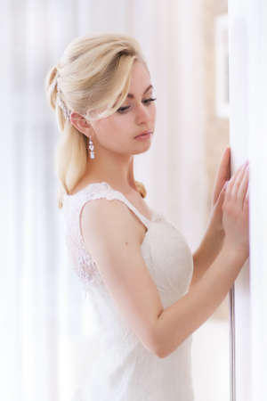 Young beautiful bride at room in light background Stock Photo