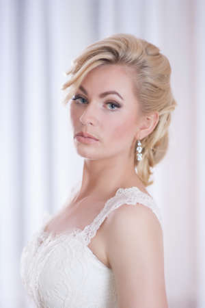 Portrait of  a young beautiful bride in light background