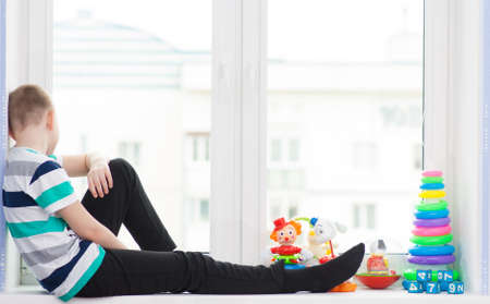 fantasize: Turning yang boy with toys on a windowsill with toys Stock Photo