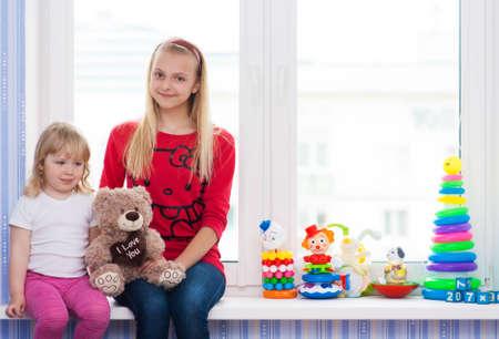 Deux copines avec un jouet assis sur le rebord de la fenêtre. Banque d'images - 58147168