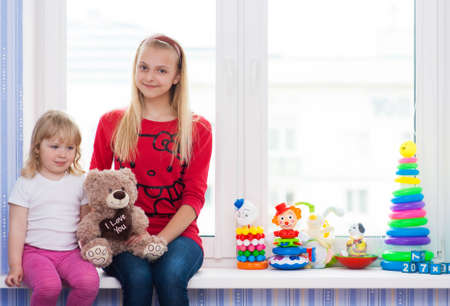 Two girlfriends with a toy sitting on the windowsill. Stock Photo