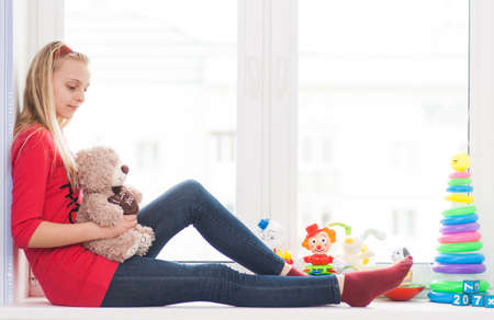 Girl sits on a window sill with toys with a teddy bear in his hands