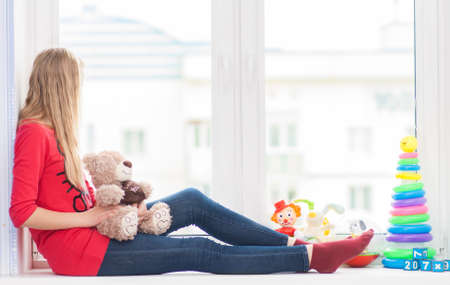 Turning girl sits on a window sill with toys with a teddy bear in his hands Stock Photo