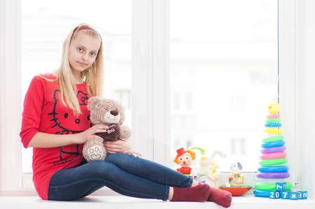Fille est assis sur un rebord de fenêtre avec des jouets avec un ours en peluche Banque d'images - 58147251
