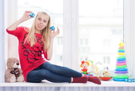 Jeune fille assise sur un rebord de fenêtre, et barbote avec des cubes Banque d'images - 58203594