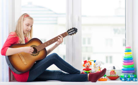 Young girl sitting on a windowsill with toys and playing guitar Stock Photo