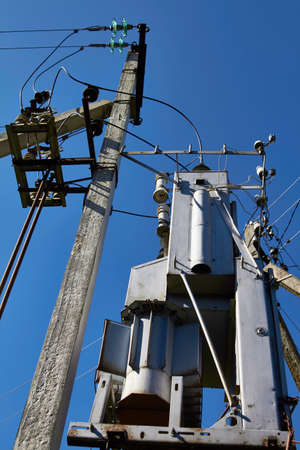 Transformer substation against a blue sky With wires and pole
