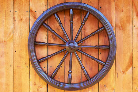 Hand spinning wheel on the wall of the old log house in the village.