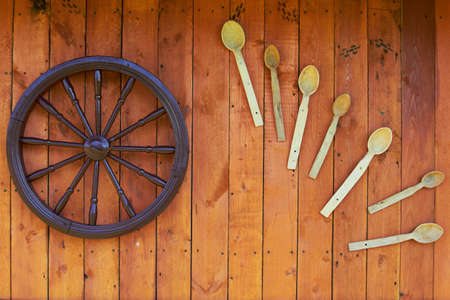 Hand spinning wheel on the wall of the old log house with old wooden spoons in the village.