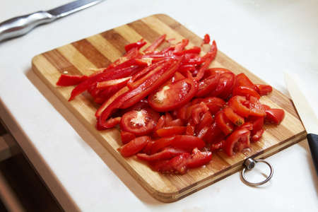 Chopped red bell pepper on a wooden cutting board. Top View Stock Photo
