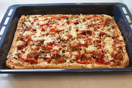 Une pizza rectangulaire sicilienne avec du fromage et tomate cerise sur une plaque de cuisson, la manière traditionnelle de servir le type sicilien. Banque d'images - 65799217