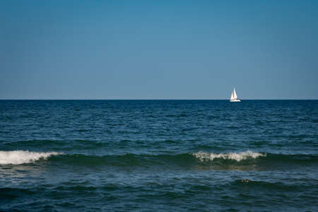 Yacht with white sails away into the sea. Waves in the foreground. Banque d'images - 110229246