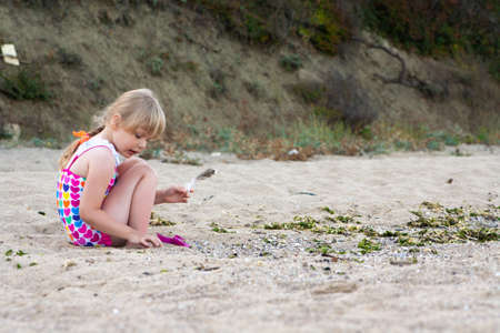 Little girl on the beach plays with sand and a feather Standard-Bild