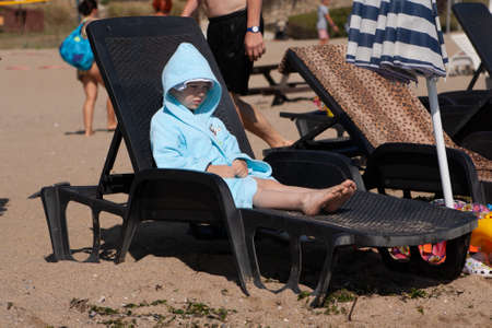 Little girl in a blue bathrobe lying in a lounger on the beach Banque d'images - 126054483