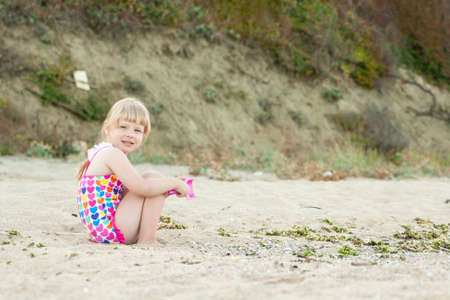 Child plays sitting on the sand at the beach on a sunny summer day. Happy little girl. Banque d'images - 126055845