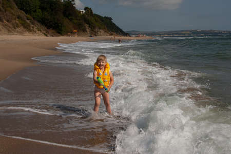 Young girl with yellow life jacket with water pistol. On the shore with the waves. Banque d'images - 126055848
