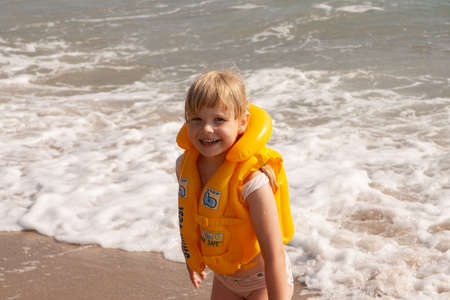 Young girl with yellow life jacket. Portrait with pretty smile. Banque d'images - 126055850