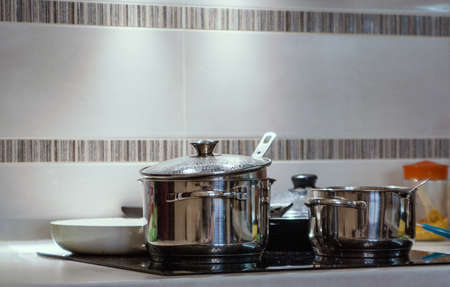 Metal pots in the kitchen on the induction cooker are brightly illuminated with directional light Banque d'images - 126055805
