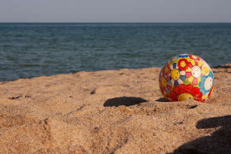 Children's multi-colored ball on the beach near the sea Banque d'images - 126054579