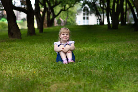 Sweet, happy little girl sitting on a grass in a park Banque d'images - 126054601