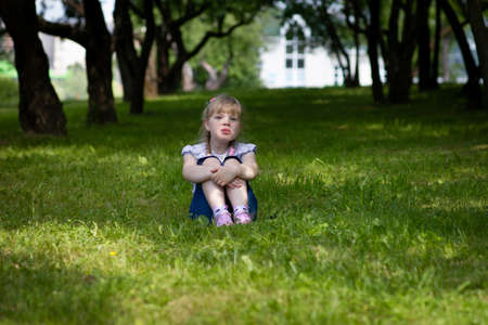 Sweet, happy little girl sitting on a grass in a park Banque d'images - 126054603