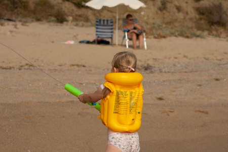 A little girl in a yellow life jacket on the beach plays with a water cannon on the shore. Bulgaria. Stok Fotoğraf