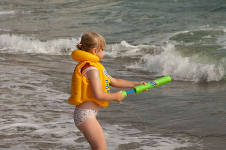 Young girl with yellow life jacket. On the shore with the waves. Black Sea.