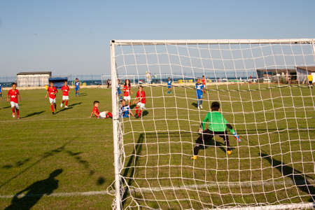 Young football players on the field play football. View from the goalkeeper. Bulgaria. Place Obzor. Sea coast.