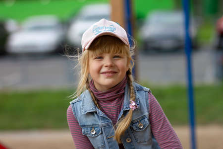 A smiling teenage girl with a slightly disheveled hairdo and a cap.