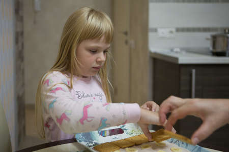A little girl in pink pajamas is making a layer cake out of cookies.