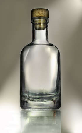 transparent glass bottle isolated on light brown background