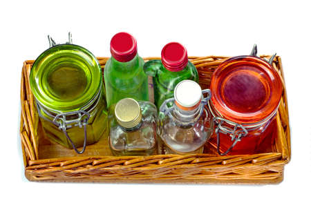Wicker tray with empty glass jars and little glass bottle, isolated on white background Banco de Imagens