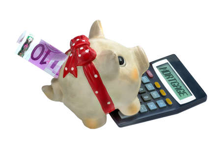 Piggy bank and calculator with the word mortgage written on it Banco de Imagens