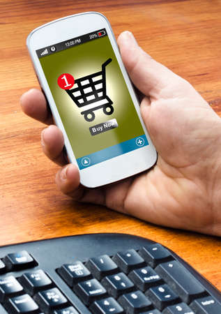 hand holding on smartphone with a online shooping (buy button on the screen) Banco de Imagens