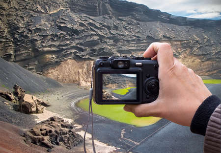 hand holding the Digital camera, taking a lanzarote landscape photo using liveview