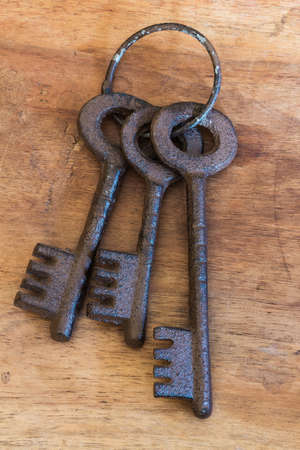 Bunch of old keys on wood background Banco de Imagens