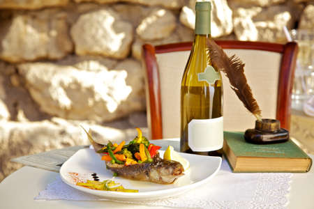stuffed fish: On the table stuffed fish with vegetables and a bottle of white wine Stock Photo