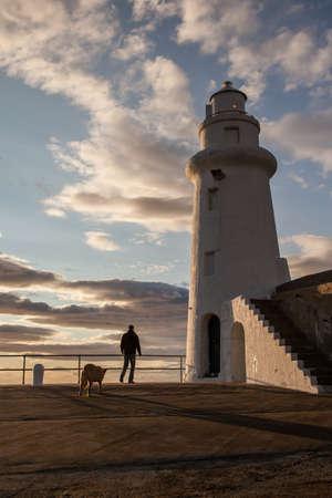lighthouse keeper: lighthouse and lighthouse keeper at sunset Stock Photo
