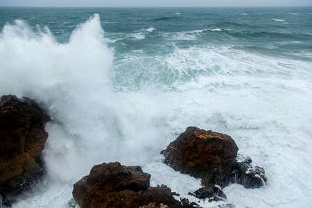 unstoppable: Atlantic storm waves splashing on rocks Algarve Coast