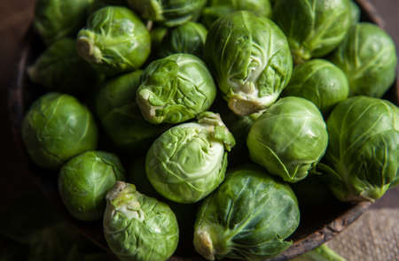 fresh Brussels Sprouts in wooden bowl on rustic background