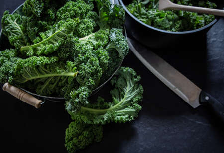 Green kale and knife isolated on black background superfood vegetables Still life