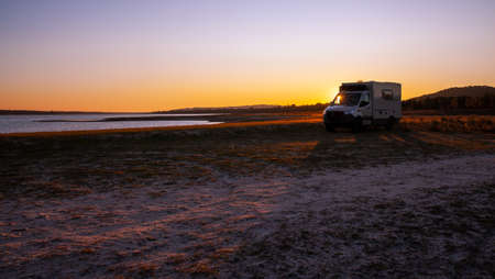 Adventure offroad travel scenery at sunset by the lake overnight stay Standard-Bild