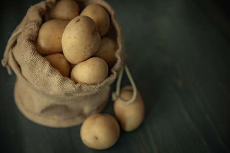 Potatoes in sackcloth on rustic wooden background on soft windows light food vintage
