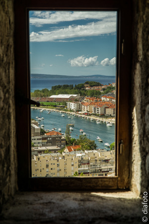 think through: Window view on a town with a river and a sea Stock Photo